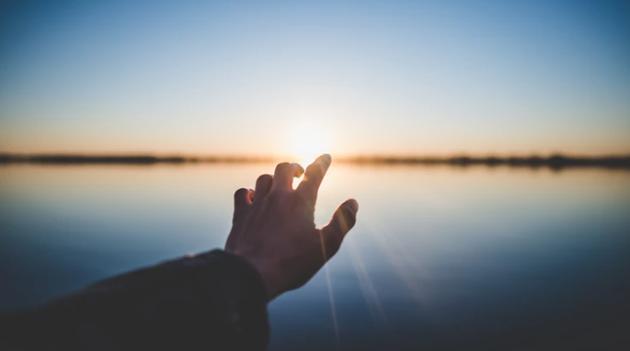 hand-towards-rising-sun